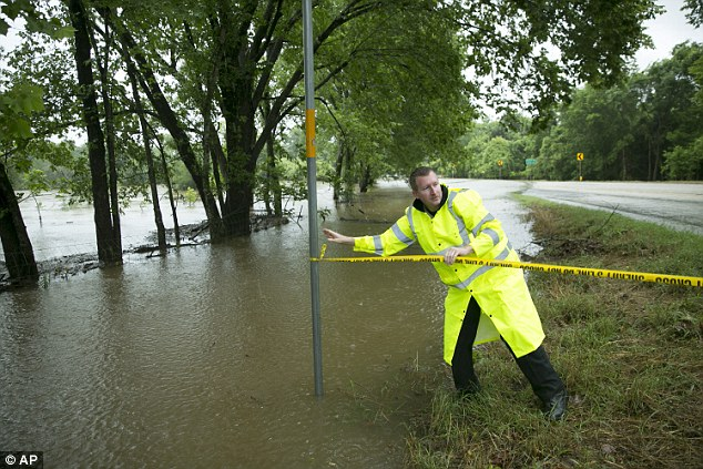 Roads remained closed all around the state on Friday as rainwater made it impossible to drive. Pictured, a sheriff deputy closes a flooded road in Smithville on Friday