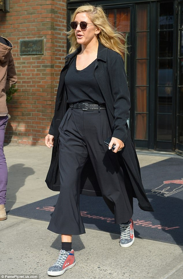 Finishing touches:An on-trend duster coat added to the look, while heavily tinted Aviator sunglasses rounded things off as she prepared for her latest appearance in New York