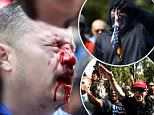 A Donald Trump supporter breaks up a scuffle during the Patriots Day Free Speech Rally in Berkeley, California as counter-protesters broke through netting separating the two groups in a park