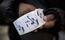 """Um mesário segura adesivo com a inscrição """"Eu votei"""", em posto de votação no Brooklyn, Nova York. Nos Estados Unidos, o voto não é obrigatório"""