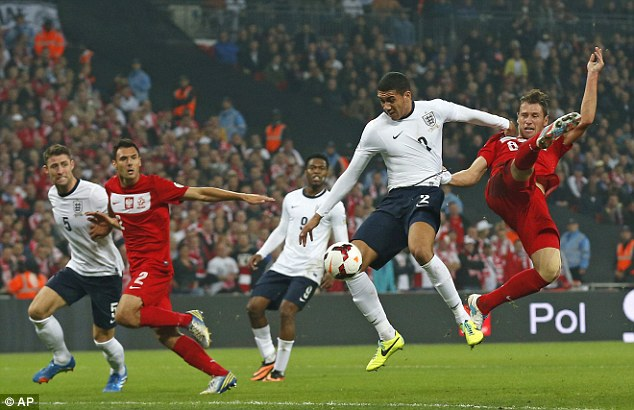Strong defence: England right-back Chris Smalling, second right, is challenged by Poland's Grzegorz Krychowiak
