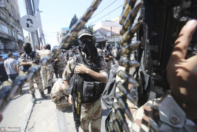 Still armed: Palestinian Islamic Jihad militants carry automatic weapons during the rally to celebrate the ceasefire this week