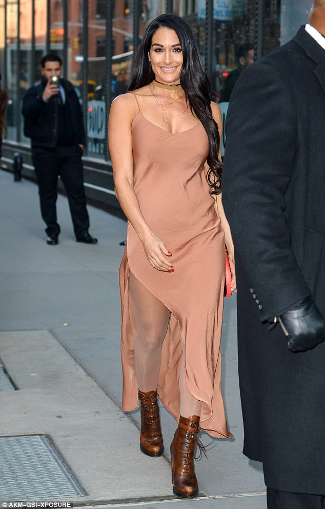 Pretty in peach: Nikki looked stunning in a peach satin dress and quirky lace up boots as she was on her way to making an appearance at SiriusXM Studios to discuss her reality series Total Divas