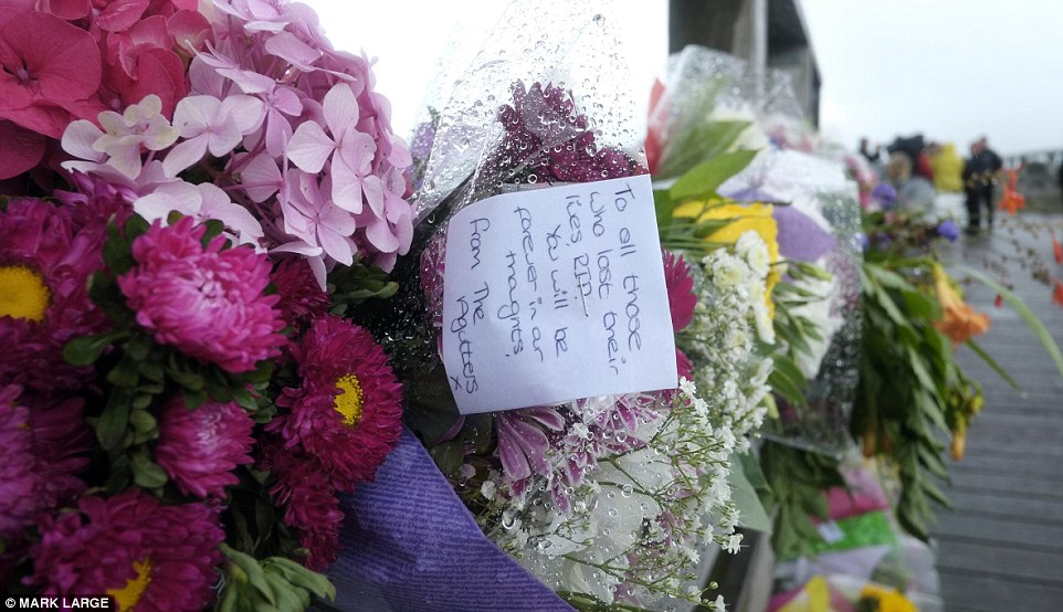 Tributes: The bridge now has bunches of flowers and other items left by mourners running its whole length