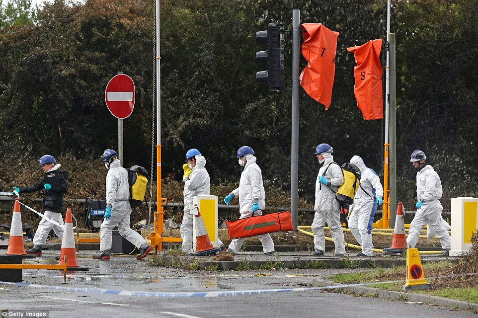 Search: Emergency service workers in protective overalls walk on to the A27 as the hunt for more victims continues