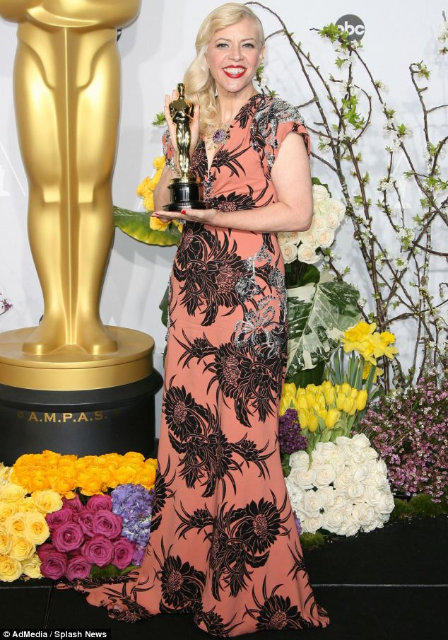 Comparatively budget conscious: Catherine Martin wore a custom-made Prada dress, worth around $25,000, while she wore just over $400,000 in Tiffany jewellery. But she pRoudly held the bling that counts - the Academy Award