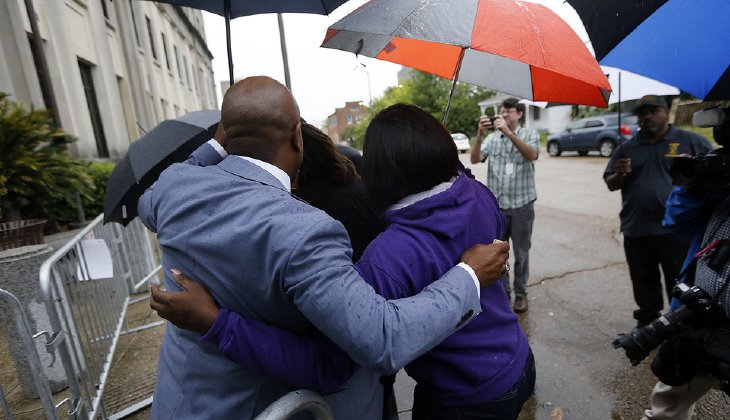 Chris Stewart, left, attorney for Alton Sterling's son Cameron Sterling and his mother Quinyetta McMillan, hugs family members of Alton Sterling as they arrive at federal court in Baton Rouge, La., Wednesday, May 3, 2017, to meet with the U.S. Justice Department officials. (AP Photo/Gerald Herbert)