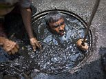 Filthy: The sewer cleaner in Dhaka has to dig around in the sludge to clean out the city's sewers, a thankless task