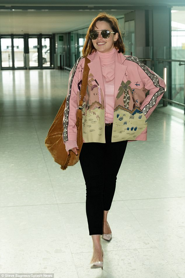 Airport chic: Emilia Clarke looked pretty in pink as she made a sartorial statement in a pink turtleneck and funky matching jacket as she prepared to jet off to New York from London on Friday