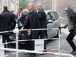 Marine Le Pen is surrounded by her bodyguards after leaving the cathedral in Reims via a back door