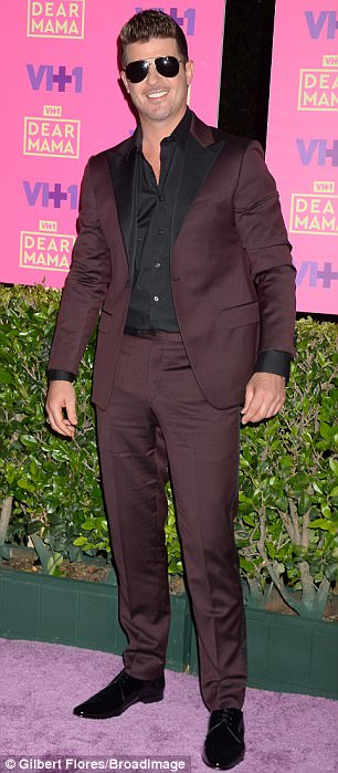 Dressed sharp: The singer looked dapper in a maroon and black suit