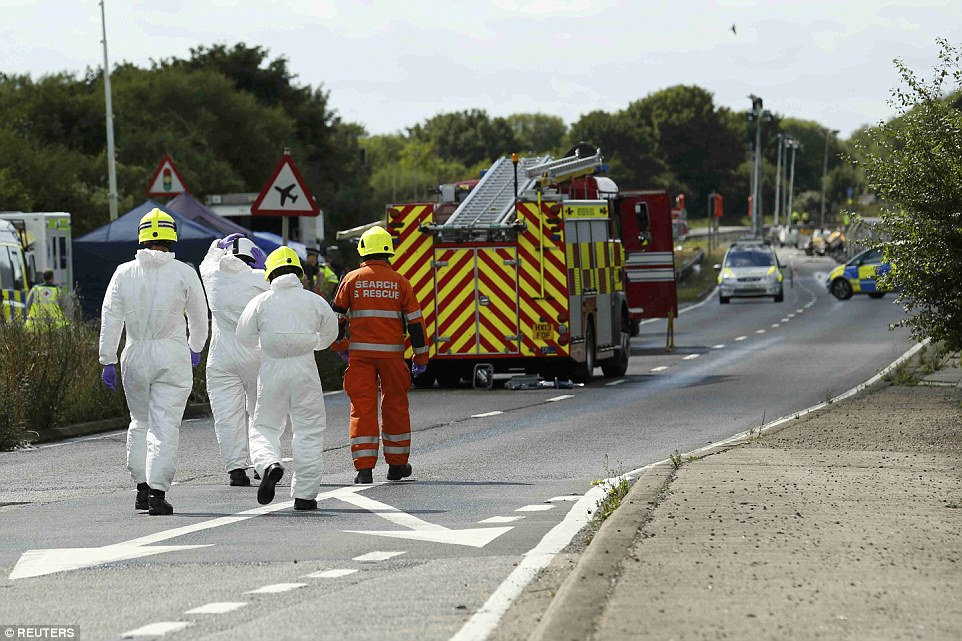 Walking: Emergency services and crash investigation officers continue to work at the site where the fighter jet crashed onto the A27