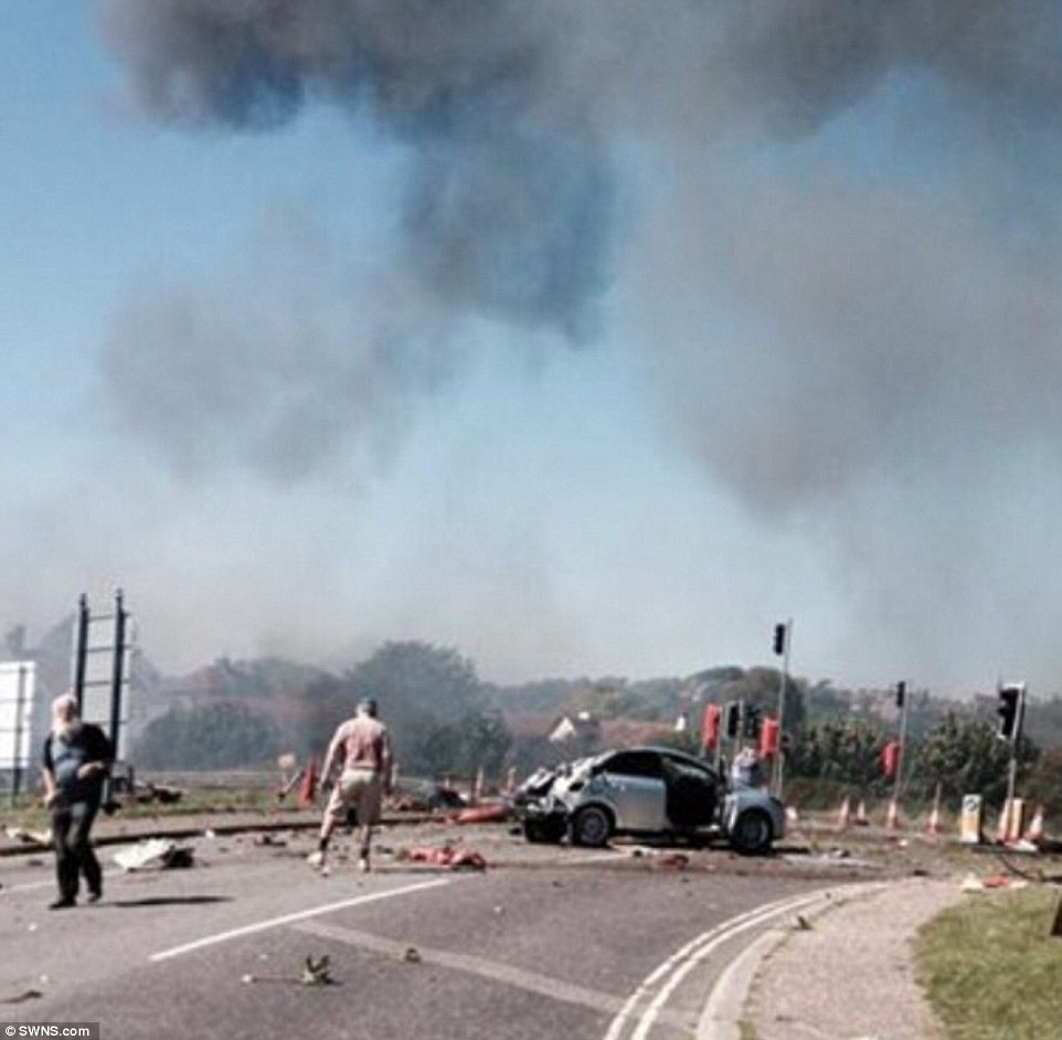 Aftermath: Moments after the crash, stunned survivors surveyed the scene of the carnage as a pall of smoke hung low over the sky