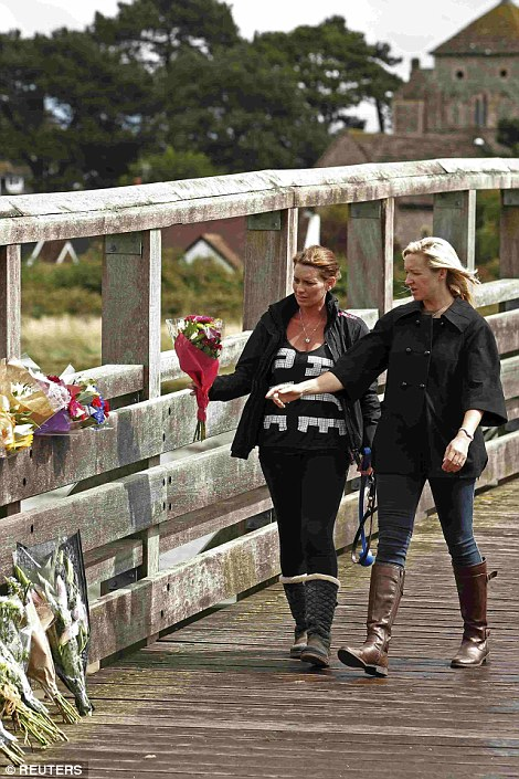 Women lay flowers near to the site where the Hawker Hunter fighter jet crashed onto the A27 road at Shoreham