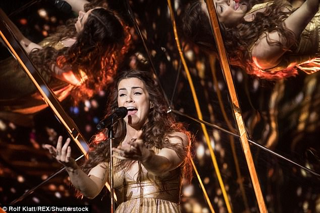 Like a Greek goddess: Lucie's metallic dress wrapped around her waist and flowed to the floor, coordinating with the golden light effects projected behind the singer