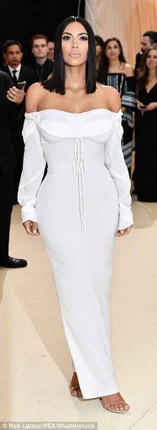 Covered up: Kim Kardashian arrived at the Met Gala on Monday in an off-the-shoulder white Vivienne Westwood dress and simple sandals