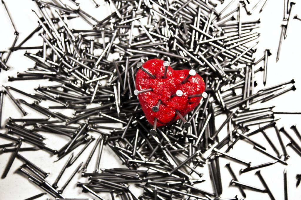 Red heart on pile of iron grey nails, pierced by a nails