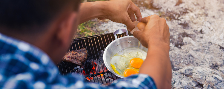 Cracking eggs into a pan over the campfire. Use budget camping gear for cooking.