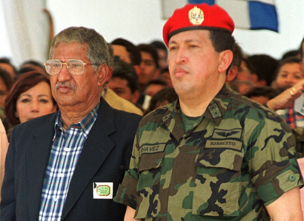 ** FILE ** In this May 22, 1999 file photo, Venezuelan President Hugo Chavez, right, and his father Hugo de los Reyes Chavez, listen to the national anthem in Puerto Nutrias, Barinas State, about 500 kilometers (310 miles) southwest of Caracas. (AP Photo/Andres Leighton, File)