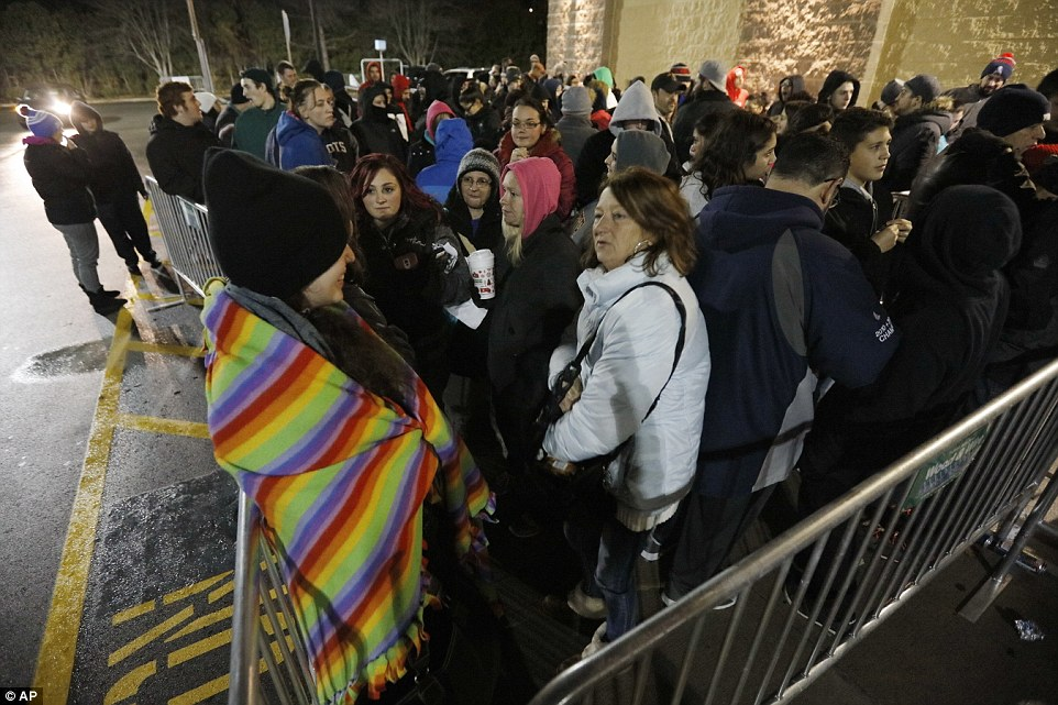 A group of people tough out the chilly weather in Dartmouth, Massachusetts as they wait for a Walmart to open on Friday
