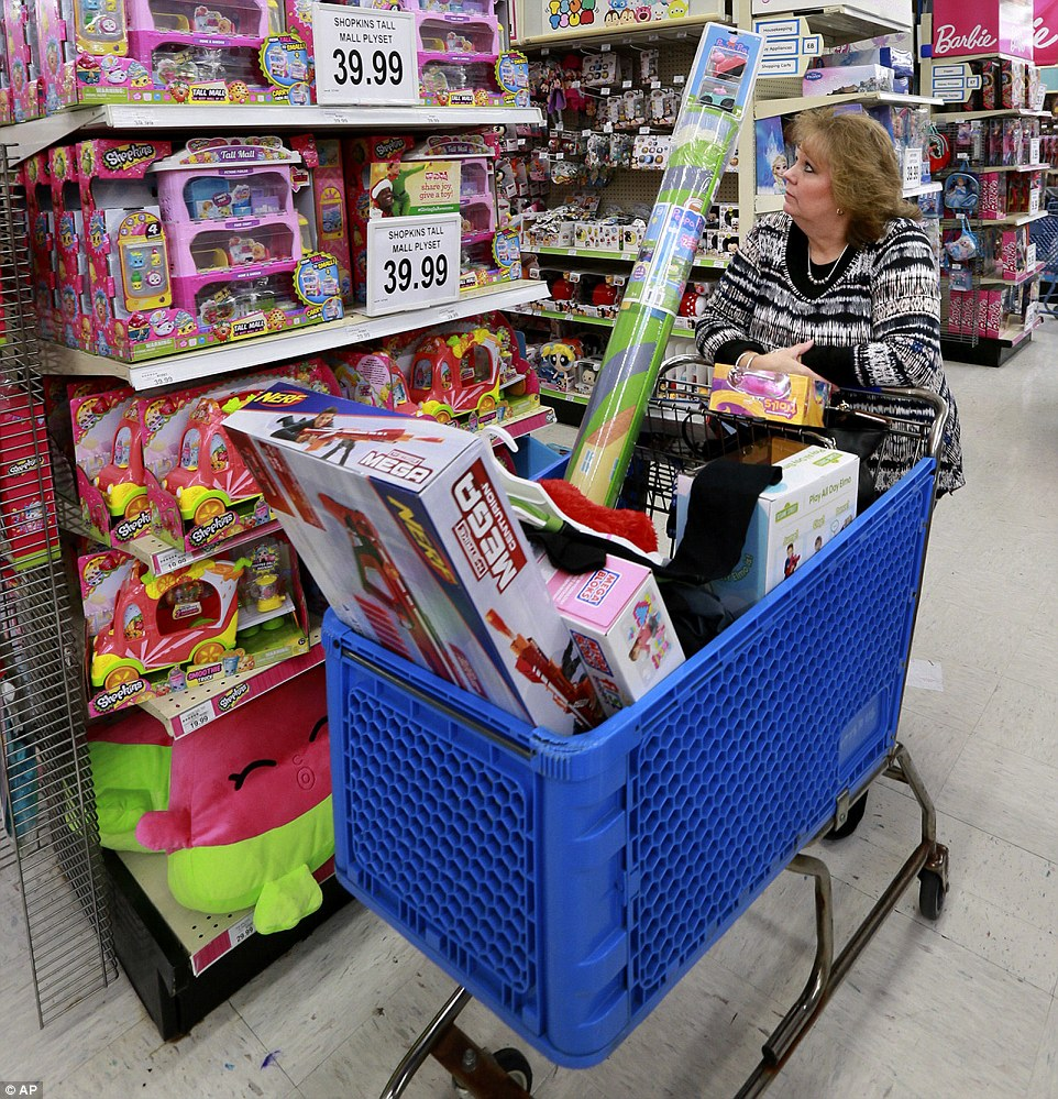 Belinda Wallace walks bast a shelve of Shopkins at the Toys R Us store in Winchester, Virginia on Black Friday