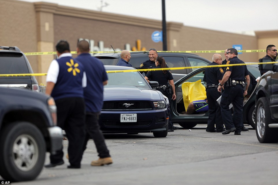 A man appears to be seen slumped in the driver seat of a car surrounded by officers after a shooting in a Walmart parking lot in San Antonio