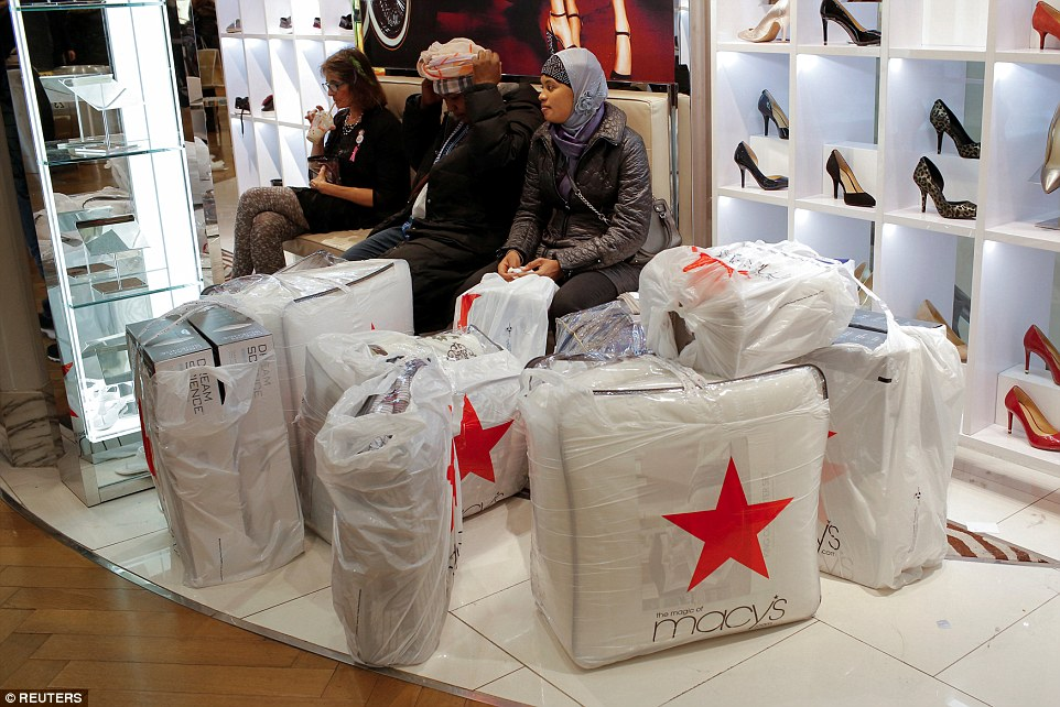 People wait with purchases at Macy's Herald Square during the Black Friday sales in Manhattan, New York on Friday