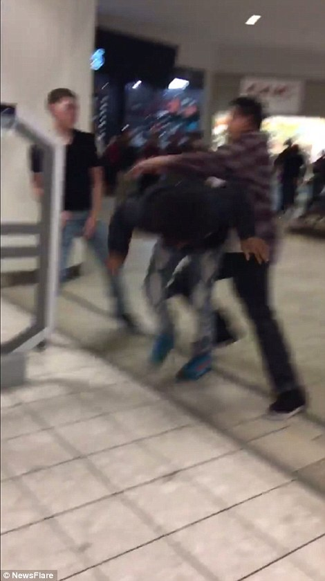 Two young people are seen engaging in a fight