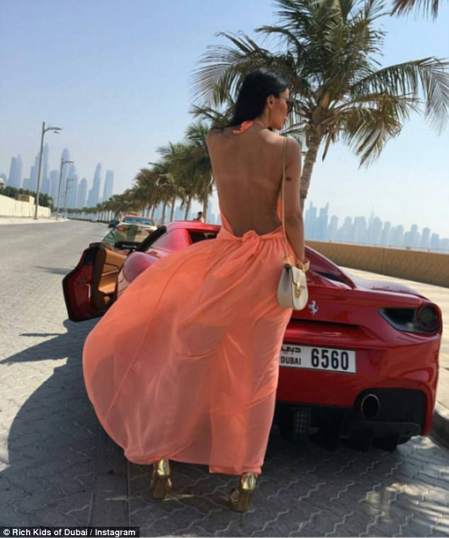 One young woman showed off her backless orange frock as she posed next to a red Ferrari