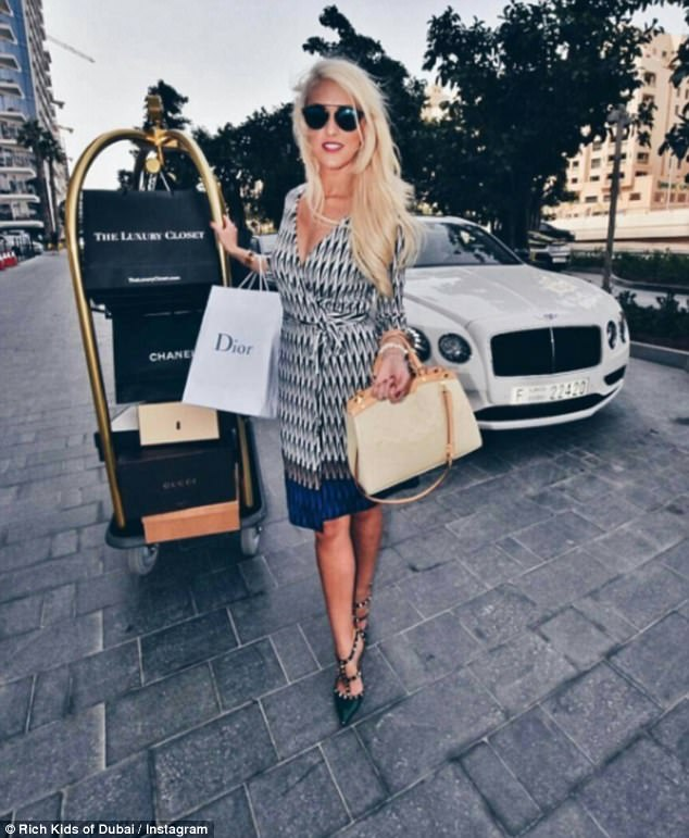 Lifestyle vlogger Alex Hirschi shows off her latest haul of designer gear while posing next to a Bentley
