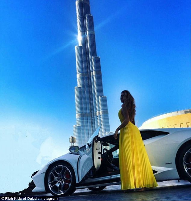 One stunning photograph shows a brunette beauty wearing a stunning yellow gown as she poses in front of her white Ferrari, with the famous Burj Khalifa next to her