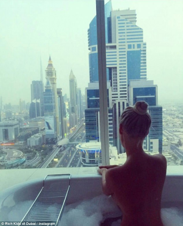 Another snap shows a young woman enjoying a bubble bath as she admired the breathtaking view over the city