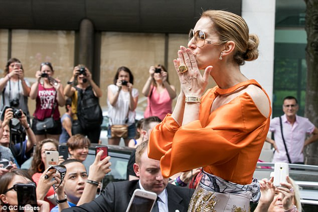 Blowing kisses: The singer stood through the sun roof of her black car to greet the throng of fans who had gathered to watch Celine leave the Royal Monceau on Sunday