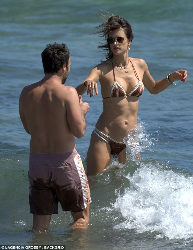 Toned:Sporting nothing but a selection of necklaces with the swimwear, Alessandra left her impressively toned stomach and gym-honed waist during a dip in the sea with her man