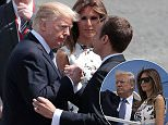 Brothers in arms: French President Emmanuel Macron (L) bids farewell to Donald Trump with a very firm hand shake as Melania watches on after the traditional Bastille Day parade in Paris