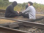 Danger: Two young people sit on the train track on by Simpson's Foot Crossing in Sittingbourne