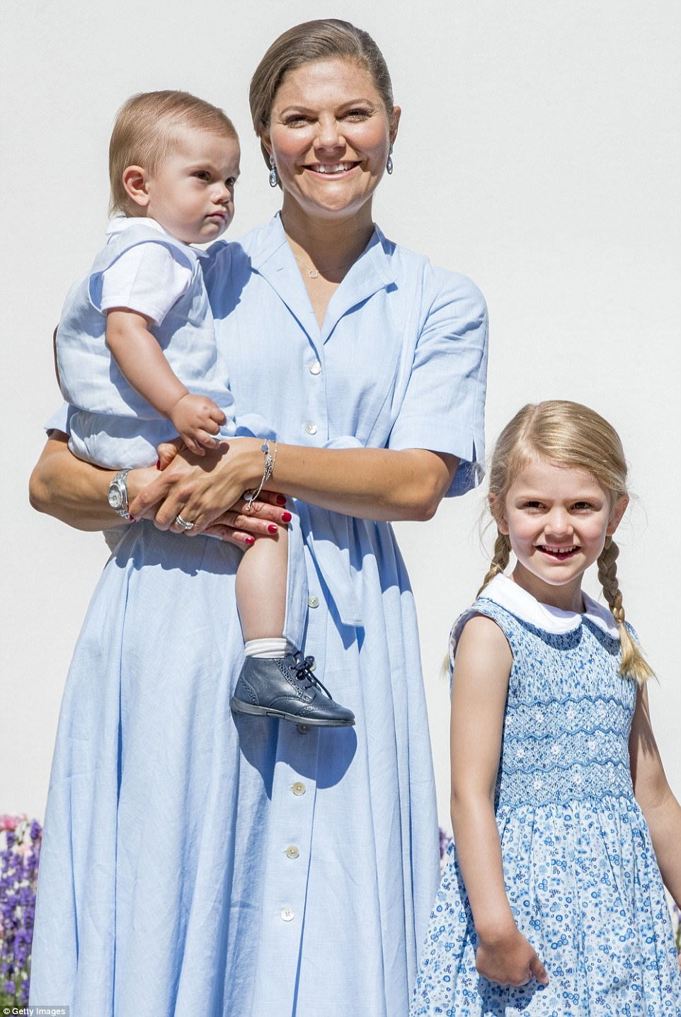 Dazzling: Princess Victoria (centre) looked radiant in a sky-blue shirt dress, with pretty pleats and a bow around the waist