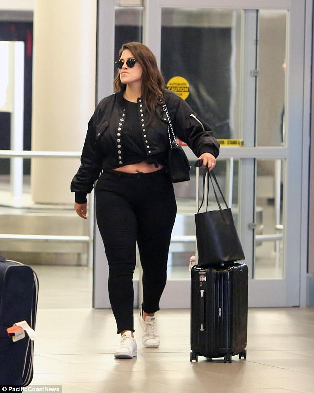 Sun's out, tum's out: The model showed off a sneak peek of her tummy while arriving at Toronto Pearson International airport on Thursday