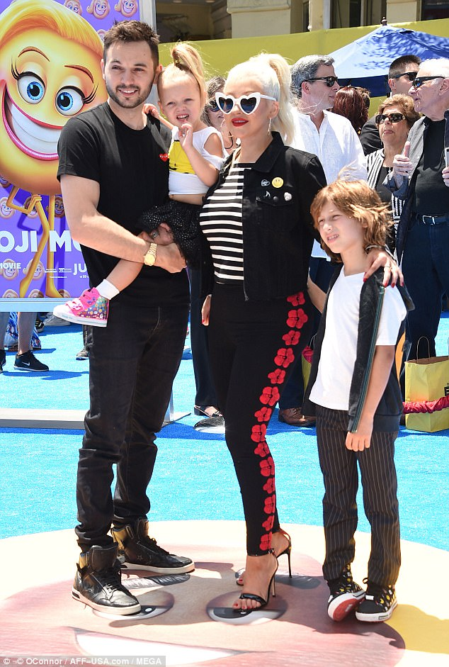 Family affair! Partner Matthew Rutler matched his love's dark duds, carrying daughter Summer while son Max stood by their side