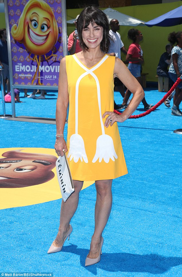 Ray of light! Constance Zimmer donned a sleeveless sunshine yellow frock with retro tulip design while carrying a white clutch that read 'feminin.'