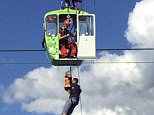A young boy was among those winched to safety after as many as 100 people were trapped inside cable cars dangling over Cologne