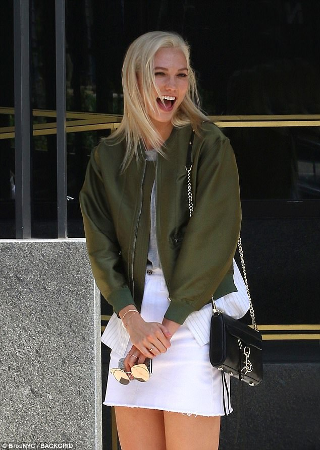 Laugh it off: Her trademark platinum tresses were left long and loose as she carried a black purse with a gold chain strap