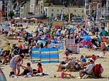 Making the most of it: A couple pictured relaxing and enjoying the sunshine on Weymouth beach in Dorset this afternoon