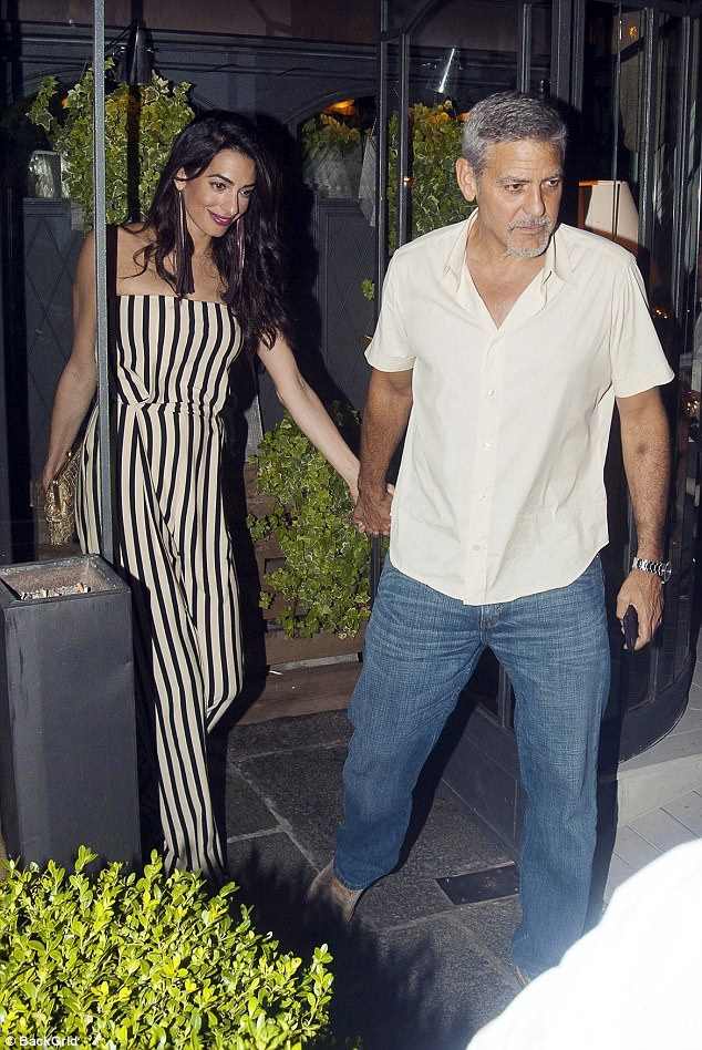 Radiant:New mother Amal looked truly stunning as she headed for dinner  in a slinky striped jumpsuit, paired with glamorous fringe drop earrings and a purple lip