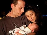 Monica Thompson is suing the hospital where her son Jacob suffocated under her in 2012 for leaving her alone with him while she was drowsy. She is pictured with the baby and her husband Graham before they turned off  his life support