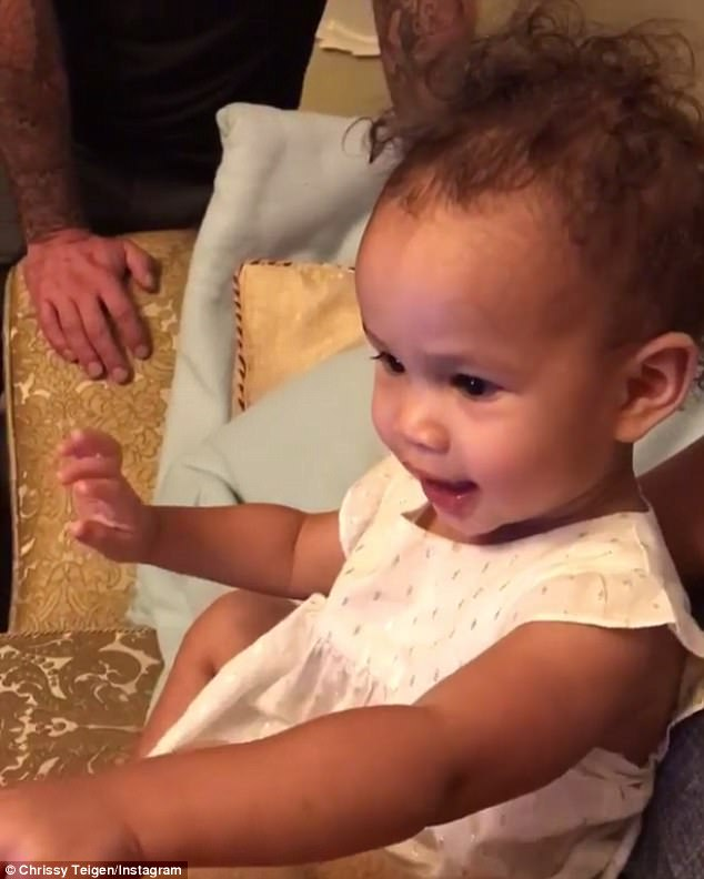 Giggling:Captivated by the recording, Luna waved to her father and gleefully giggled as she watched the video alongside her mother and several family friends