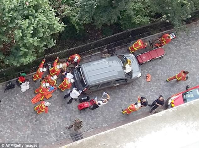 Emergency operation: Paramedics and security services gather at the scene wherea BMW slammed into six soldiers outside their barracks in a northwestern suburb of Paris