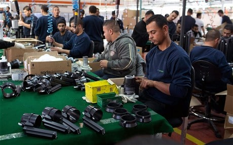 Palestinians work at a SodaStream factory on January 30, 2014 in the Mishor Adumim industrial park