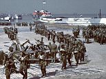 The Day: Canadian infantry soldiers are seen disembarking several craft tank ships in a low tide on June 6, 1944, surrounded by armored tanks and beach obstacles, the men walk on a carpet of wooden slats on the sand