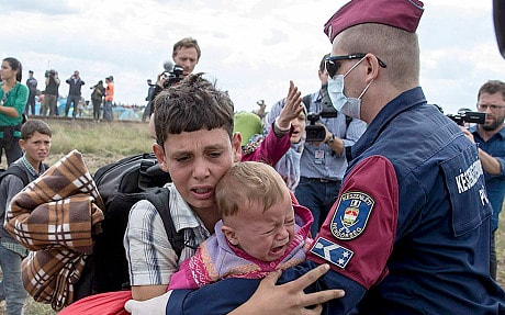 A migrant carrying a baby is stopped by a Hungarian policeman as he tries to escape a collection point in Roszke village, Hungary